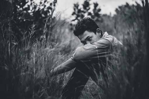 guy sitting in long grass